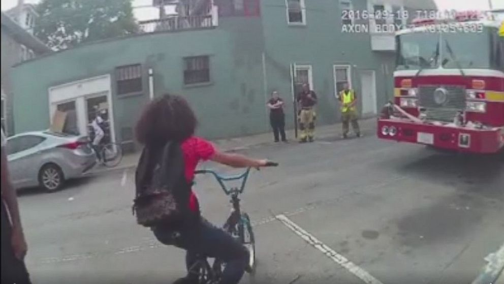 A 15-year-old girl attempts to ride her bike away from police as they investigate a traffic accident in Hagerstown, Maryland on Sept. 21, 2016.