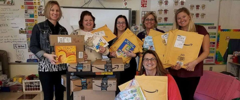 PHOTO: Tina DuBrock, kneeling, poses with fellow teachers holding books delivered to Protsman Elementary School in Dyer, Ind.