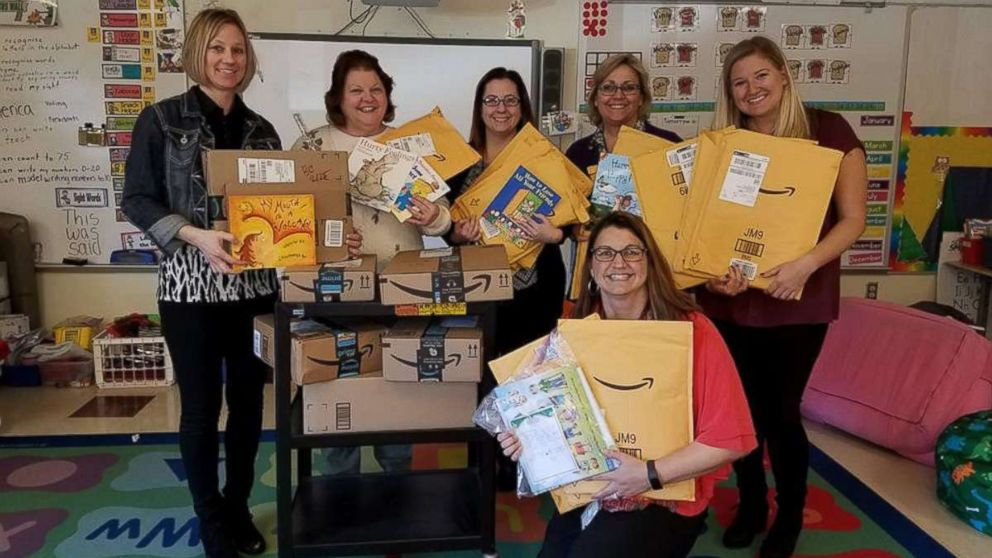 Tina DuBrock, kneeling, poses with fellow teachers holding books delivered to Protsman Elementary School in Dyer, Ind.