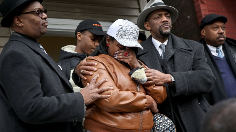 LaTarsha Jones, center, daughter of Bettie Jones, is comforted by family and friends during a press conference, Dec. 27, 2015, in front of the house where Bettie Jones was killed in Chicago on Saturday.