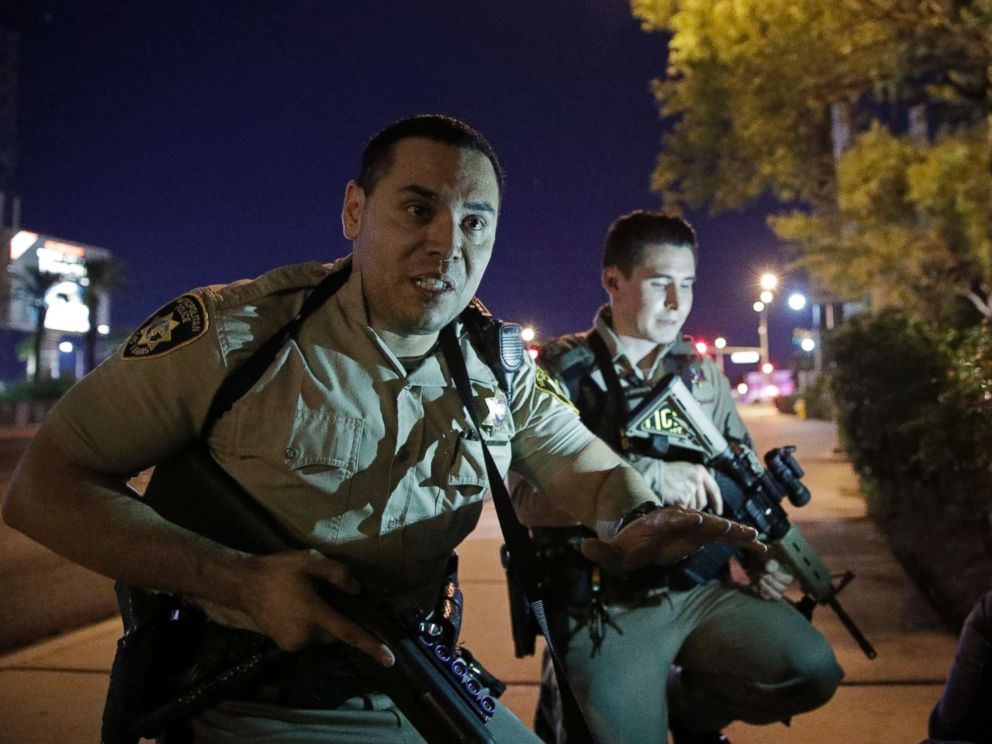 PHOTO: Police officers advise people to take cover near the scene of a shooting near the Mandalay Bay resort and casino on the Las Vegas Strip, Sunday, Oct. 1, 2017, in Las Vegas.