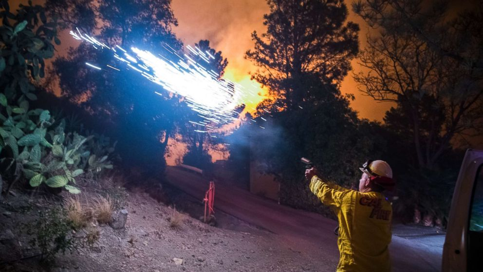 Cal Fire battalion chief and strike team leader Gino DeGraffenreid fires off flares to start a backburn to protect homes on Dec. 11, 2017 in Toro Canyon, Calif., at the Thomas Fire.
