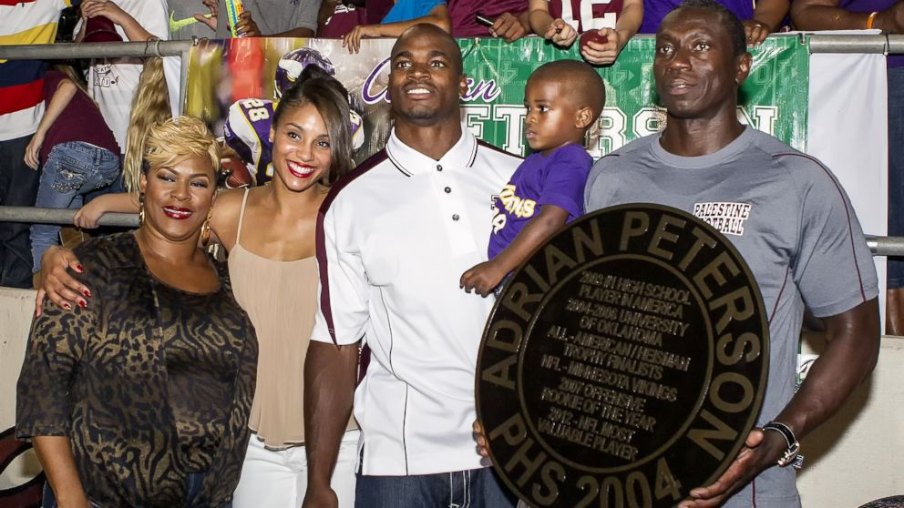 Adrian Peterson and his family retire his high school football uniform at Palestine High School in Palestine, Texas, Oct. 4, 2013.