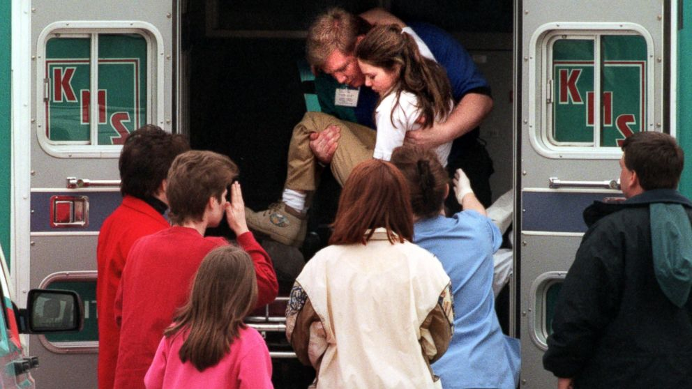 An emergency worker carries a young girl from an ambulance outside Westside Middle School in Jonesboro, Ark., Mar. 24, 1998. Four classmates and a teacher were killed when Mitchell Johnson and Andrew Golden opened fire on students and teachers at the school.