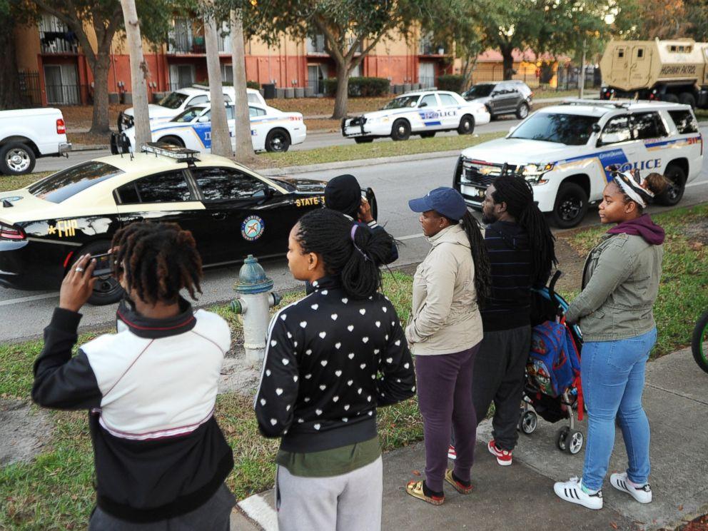 PHOTO: Residents watch as police search the Tzadik Brookside apartment complex in Orlando, Florida, for Markeith Loyd, a suspect in the shooting death of an Orlando, Florida police officer, on Jan. 9, 2017, outside an Orlando Walmart store.