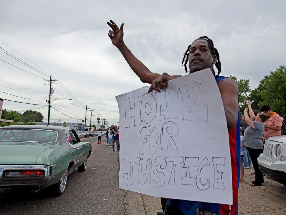 PHOTO: Protesters outside the Triple S convenience store hold signs July 6, 2016, supporting justice for Alton Sterling, a black man who was shot and killed there by Baton Rouge Police officers.