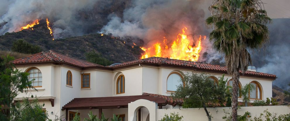 PHOTO: Fire encroaches on a home east of Los Angeles, June 20, 2016, in Duarte, Calif.