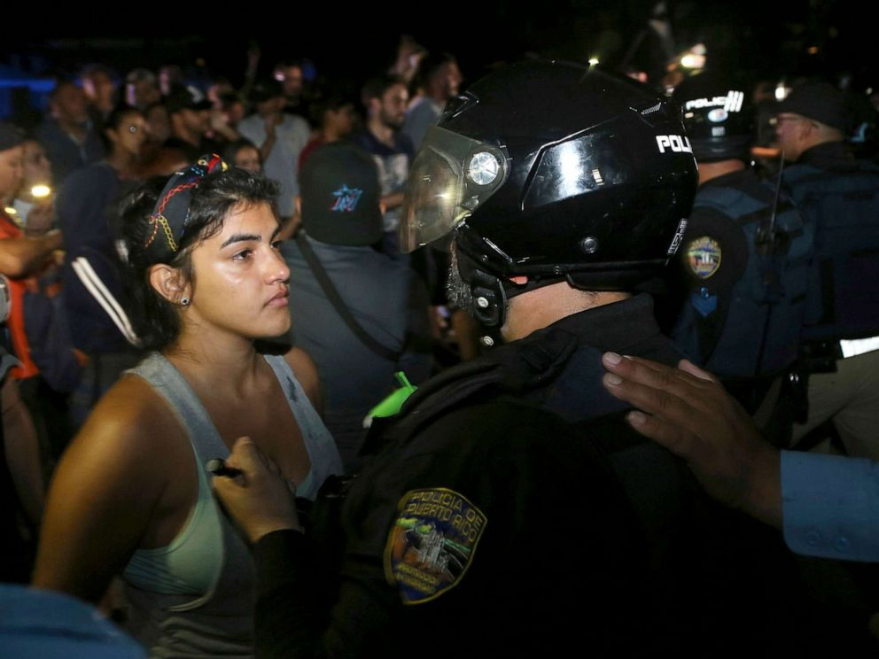 PHOTO: A protester confronts a police officer who is part of a battalion blocking the gate of the Yolanda Guerrero Cultural Center in Guaynabo, Puerto Rico, July 21, 2019.
