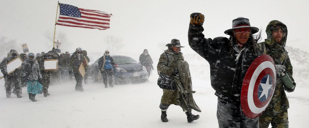 """PHOTO: Veterans join activists in a march to Backwater Bridge just outside the Oceti Sakowin camp during a snow fall as """"water protectors"""" continue to demonstrate against plans to pass the Dakota Access pipeline, Cannon Ball, North Dakota, Dec. 5, 2016."""