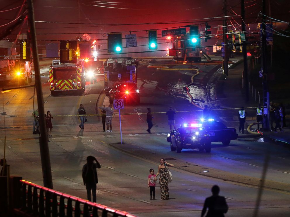 PHOTO: People make their way away from the bridge fire on Piedmont Road as emergency personnel work the scene of a bridge collapse at I-85 in Atlanta, Georgia, March 30, 2017.