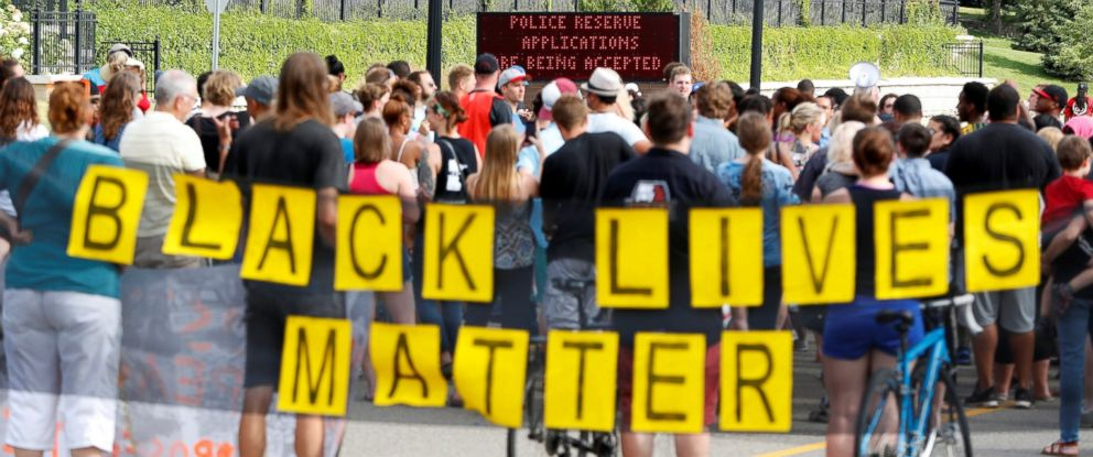 "PHOTO: Demonstrators carry a ""Black Lives Matter"" banner and protest the shooting death of Philando Castile as they gather in front of the police department in St Anthony, Minnesota, U.S., July 10, 2016."