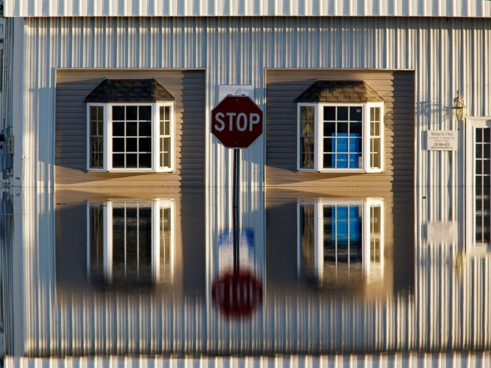 PHOTO: A building and street signs are reflected in flood waters as the Tar River rises to dangerous levels in the aftermath of Hurricane Matthew, in Tarboro, North Carolina, on Oct. 13, 2016.