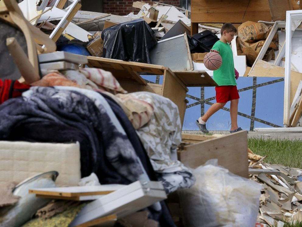PHOTO: Noah Slayton, 9, dribbles a basketball in between piles of debris in front of his flood damaged home at the South Point subdivision in Denham Springs, Louisiana, Aug. 22, 2016.