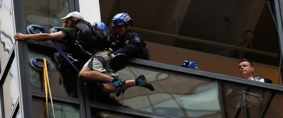 PHOTO:Officers from the NYPD embrace a man to stop him from climbing the outside of Trump Tower in New York, Aug. 10, 2016.