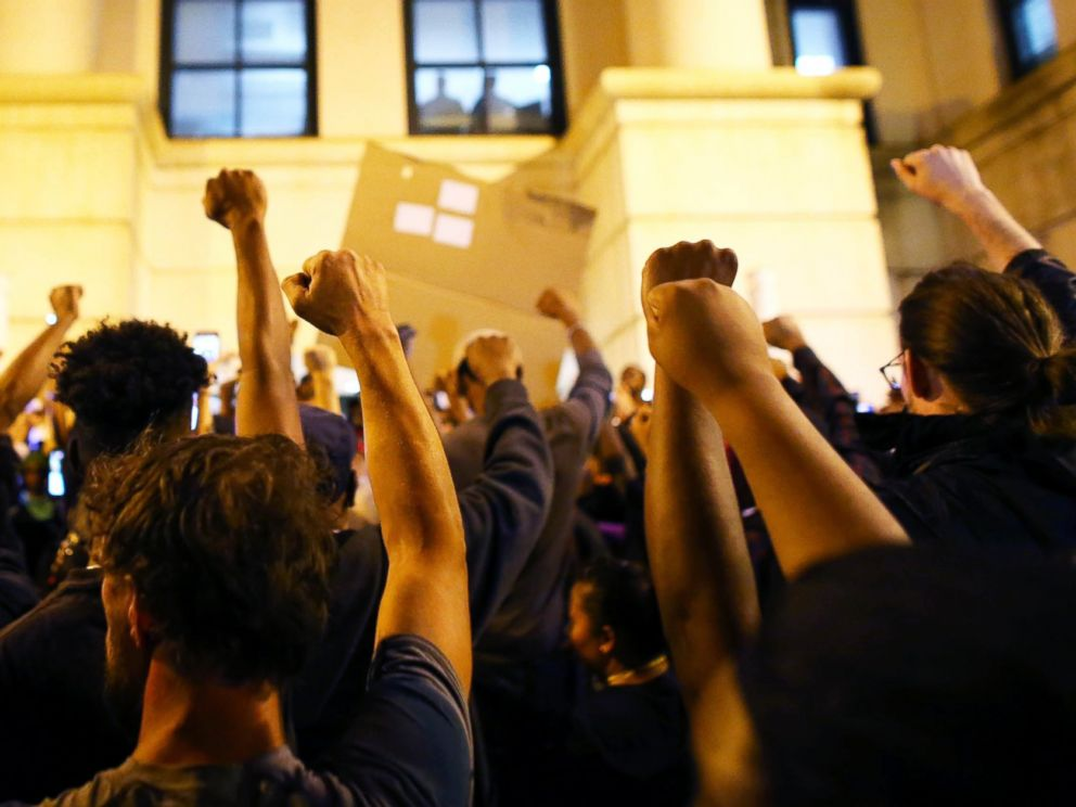 PHOTO: Protesters hold a moment of silence at the police station for a protester that died during protests September 21 during another night of protests over the police shooting of Keith Scott in Charlotte, North Carolina, Sept. 22, 2016.