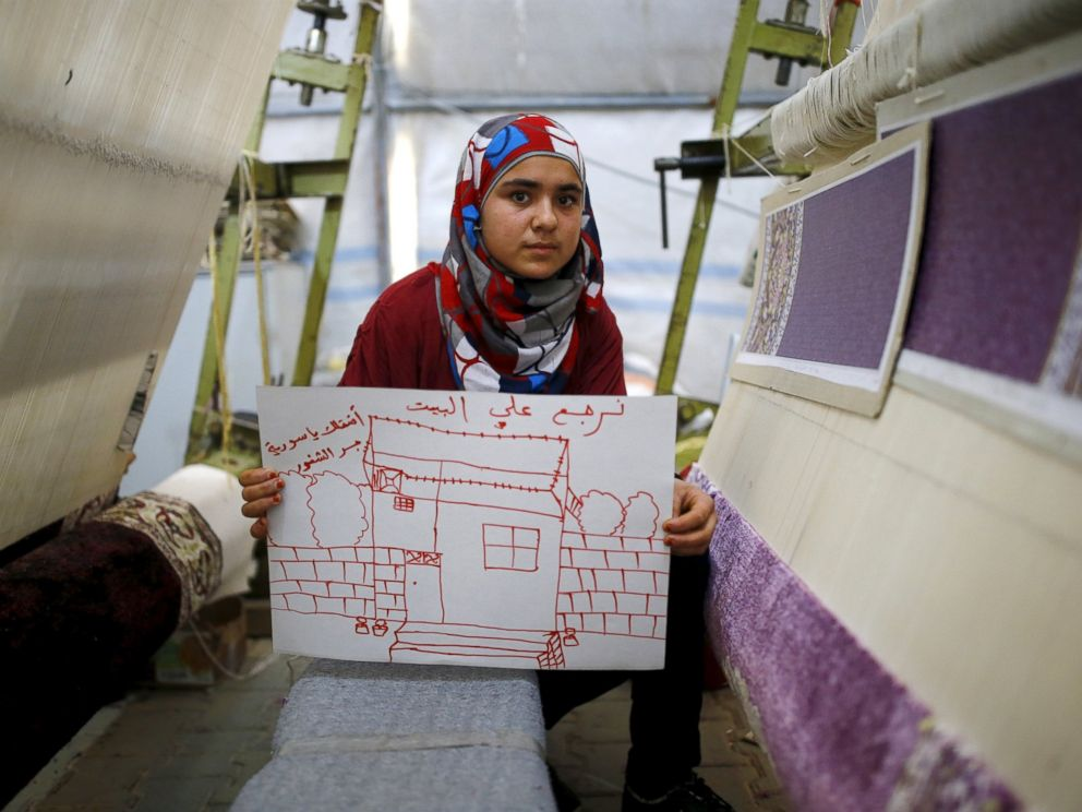 PHOTO: Syrian refugee Meryem Mahmo, 14, shows a drawing of her home during a carpet weaving workshop in Midyat refugee camp in Mardin province, Turkey, Dec. 14, 2015. The Arabic writing on the picture reads: I want my home. I miss you Syria.
