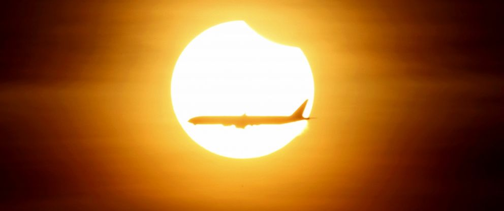PHOTO: An airplane flies past the sun as it goes into a partial solar eclipse in Singapore, March 9, 2016.