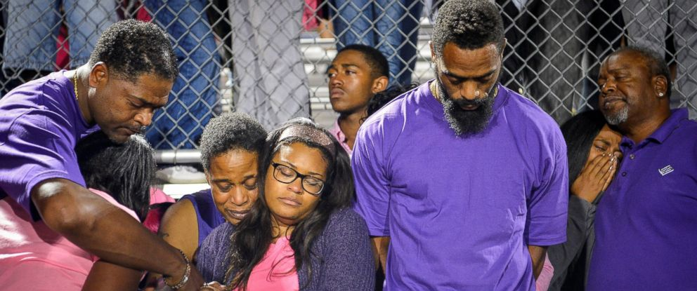 PHOTO: Shoshana Boyd, center-left, and Olympic sprinter Tyson Gay, center-right, stand surrounded by family and friends during a candlelight vigil at Lafayette High School for their daughter Trinity Gay, in Lexington, Kentucky, Oct. 17, 2016.
