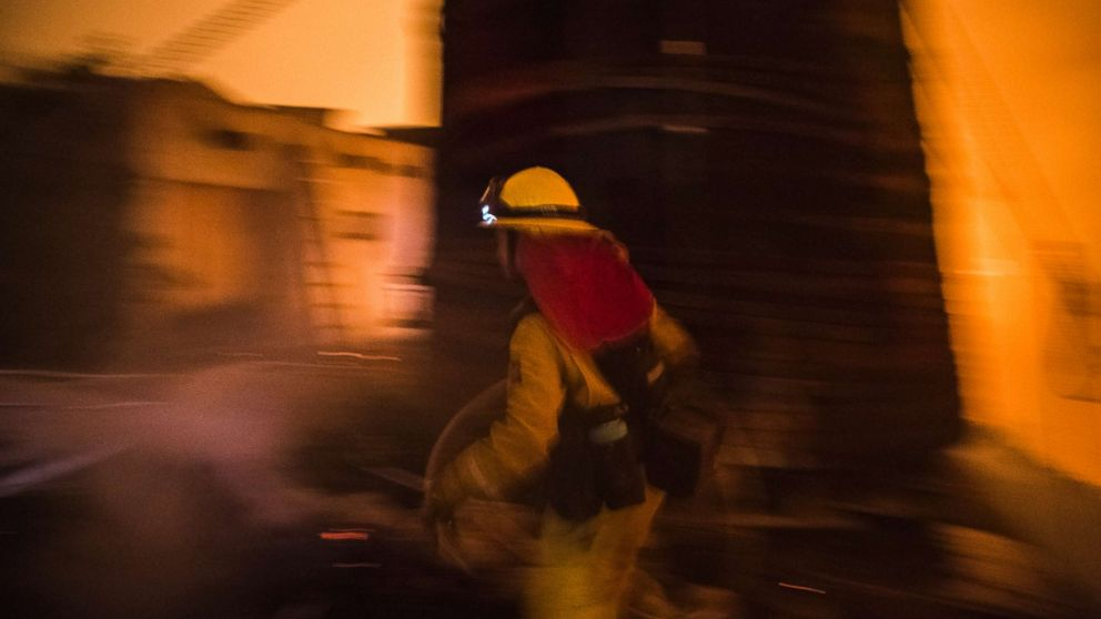 A Cal Fire firefighter races to protect a structure in upper Toro Canyon, Calif. on Dec. 11, 2017. The home was saved but the water tank burned down the next morning due to a constant flow of embers.