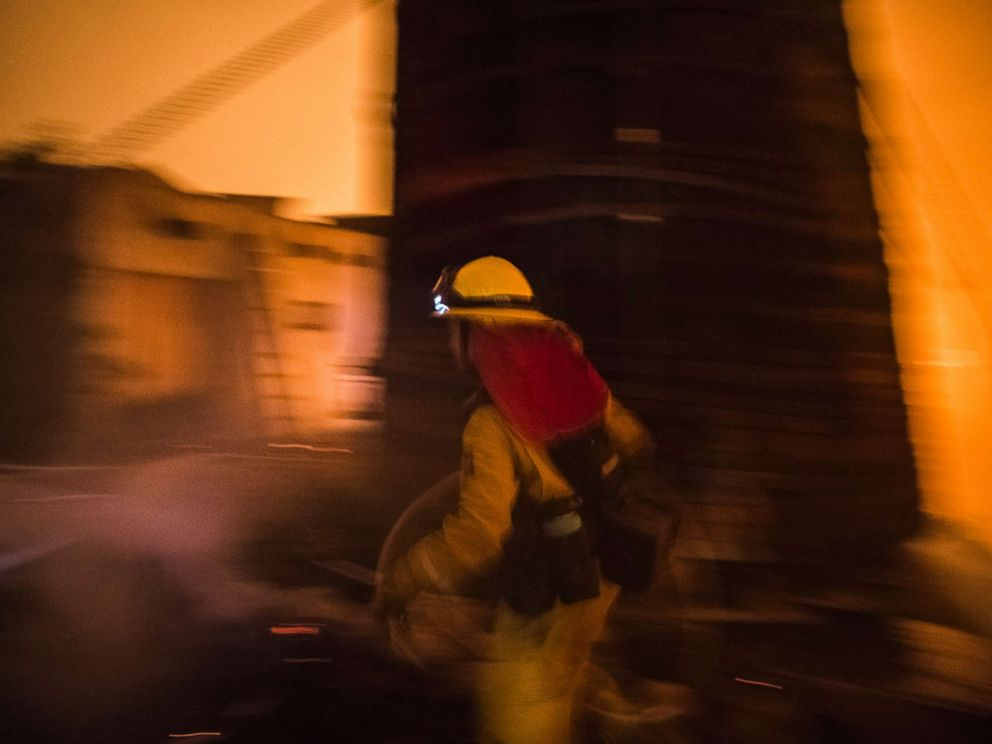PHOTO: A Cal Fire firefighter races to protect a structure in upper Toro Canyon, Calif. on Dec. 11, 2017. The home was saved but the water tank burned down the next morning due to a constant flow of embers.