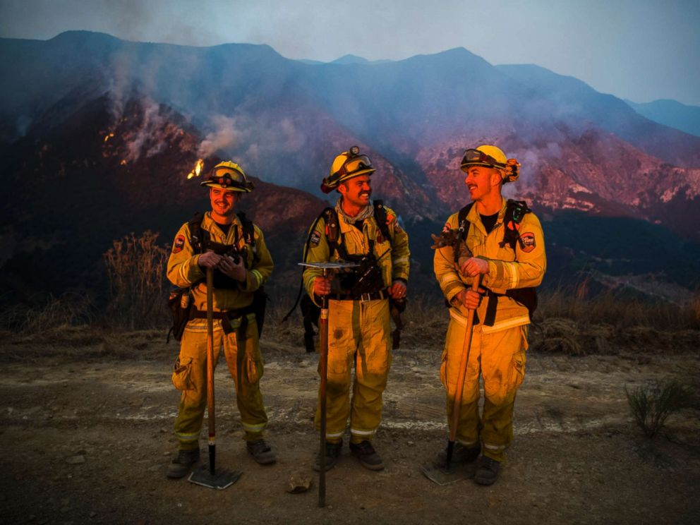 PHOTO: Firefighters Jesse Prins, Clinton Frazell, and Jesse Cole from a Cal Fire strike team dispatched from Lake County, Calif., take a moment to observe the last air tanker drops of the day during sunset on Dec. 11, 2017.