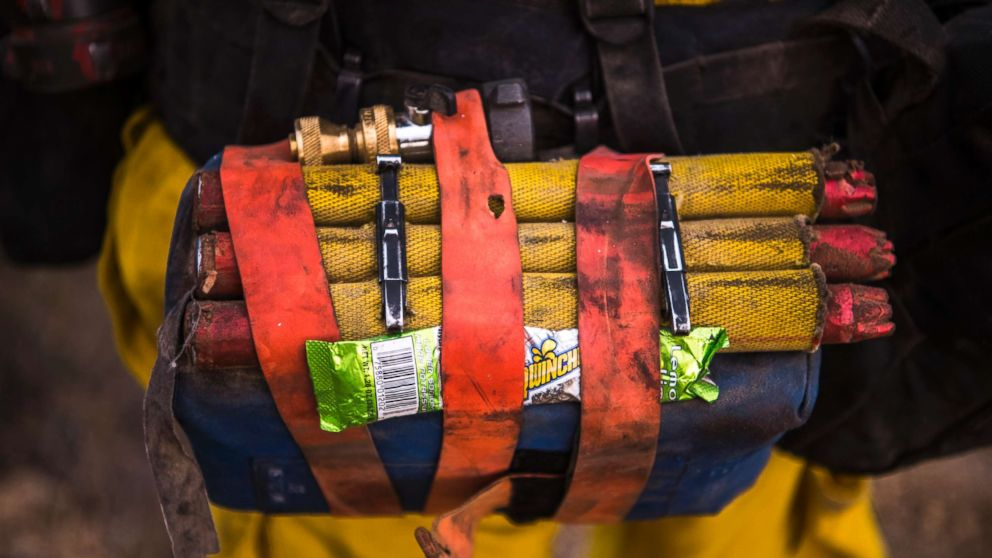 A Cal Fire wildland firefighter carries a fire shelter, fusees, hose nozzle, and powdered sports drink mix in their web gear. The Thomas Fire burns in Toro Canyon in the hills above Montecito, Calif. on Dec. 11, 2017. By nightfall the fire had burned 230,000 acres and was 15% contained, destroying nearly 800 homes.