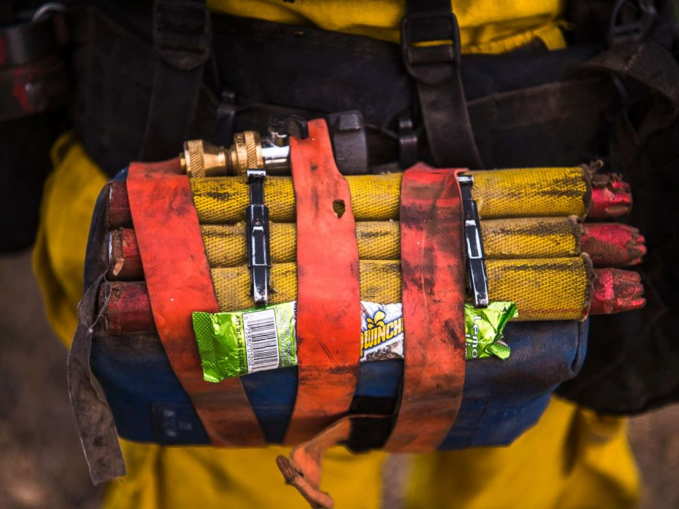 PHOTO: A Cal Fire wildland firefighter carries a fire shelter, fusees, hose nozzle, and powdered sports drink mix in their web gear.