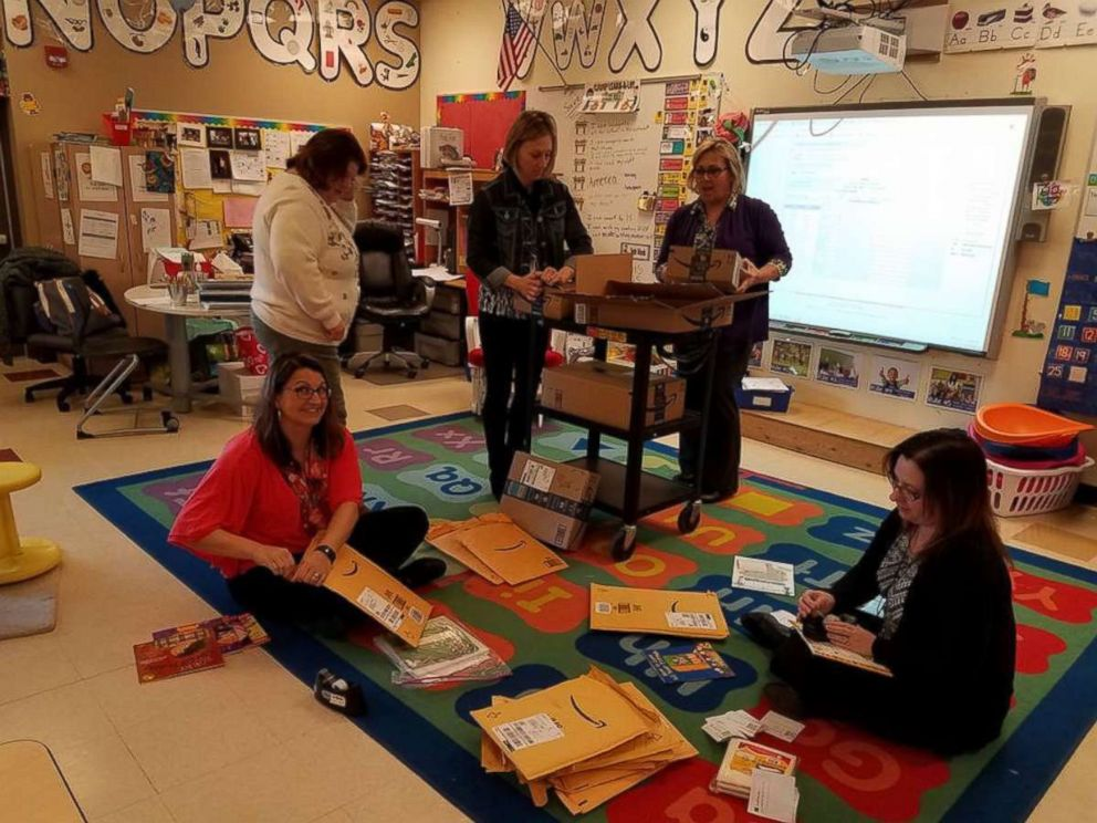 Tina DuBrock, seated left, opens books donated to her elementary school in Indiana.