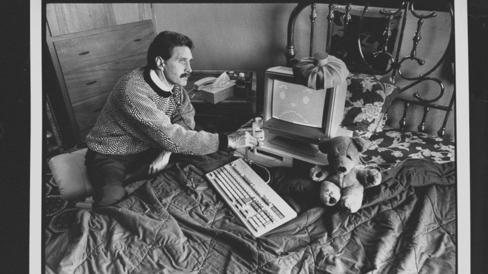 Computer analyst John McAfee holding stethoscope to IBM type computer sitting on bed w. ice bag on top, illustrating computer virus which McAfee is able to eradicate; at home.