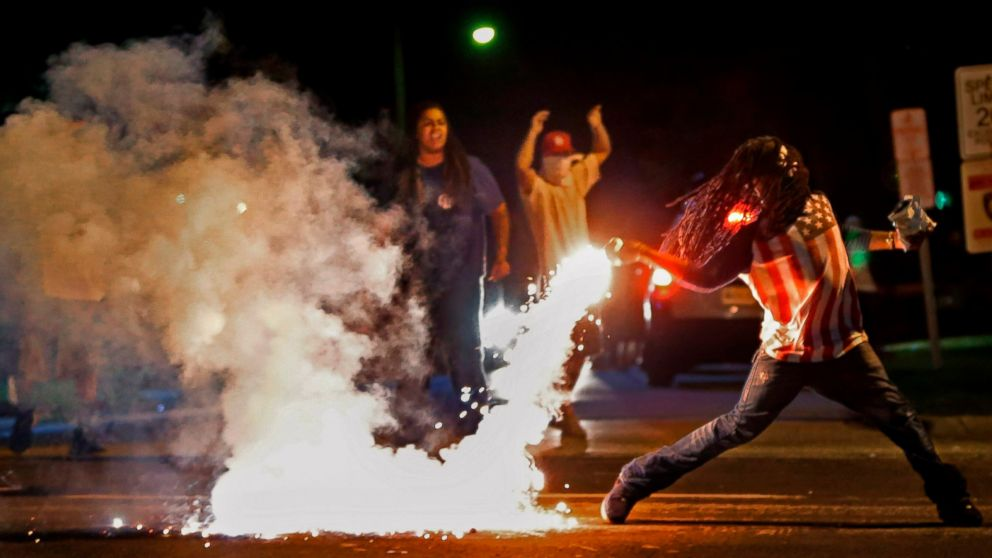 FILE - In this Aug. 13, 2014, file photo Edward Crawford Jr., returns a tear gas canister fired by police who were trying to disperse protesters in Ferguson, Mo. Six young men with connections to the Ferguson protests, including Crawford, have died, drawing attention on social media and speculation in the activist community that something sinister is at play. Police say there is no evidence the deaths have anything to do with the protests and note that only two were homicides. But activists and observers remain puzzled and wonder if they'll ever get answers. Crawford fatally shot himself in May 2017 after telling acquaintances he had been distraught over personal issues, police said. (Robert Cohen/St. Louis Post-Dispatch via AP, File)