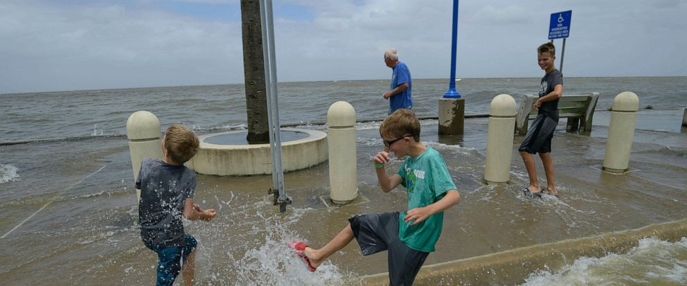 Brothers Brantley, 7, left, Brody, 8, and Bryce OHara, 11, play in the waves on Lakeshore Drive With their grandfather Rick OHara in New Orleans, La., Friday, July 12, 2019, as water moves in from Lake Pontchartrain from the storm surge from Tropic
