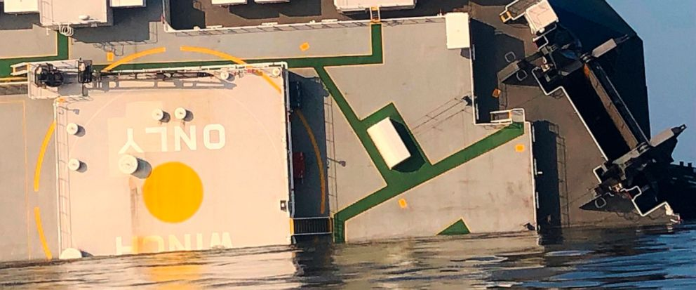 In this image released by the U.S. Coast Guard, a USCG helicopter hovers over an overturned cargo ship in St. Simons Sound, Ga., Monday, Sept. 9, 2019. The U.S. Coast Guard says rescuers have heard noises from inside the ship where multiple crew memb
