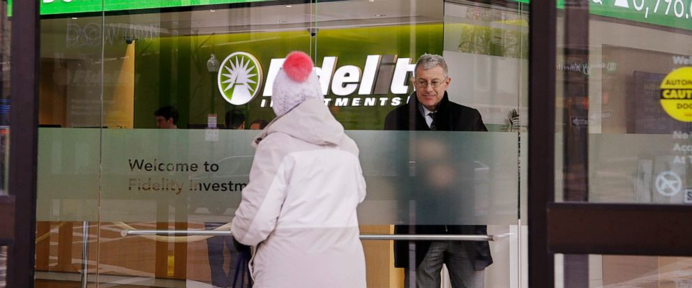FILE - In this Feb. 6, 2018, file photo, a woman walks through the front doors at a Fidelity Investments office on Congress Street as the ticker displays stock market numbers in Boston. Federal regulators are moving to require that brokers provide th