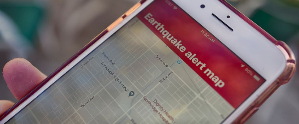 FILE - In this Jan. 3, 2019 file photo a mobile phone customer looks at an earthquake warning application on their phone in Los Angeles. Los Angeles Mayor Eric Garcetti says the citys earthquake early warning app will now alert users of weaker shaki