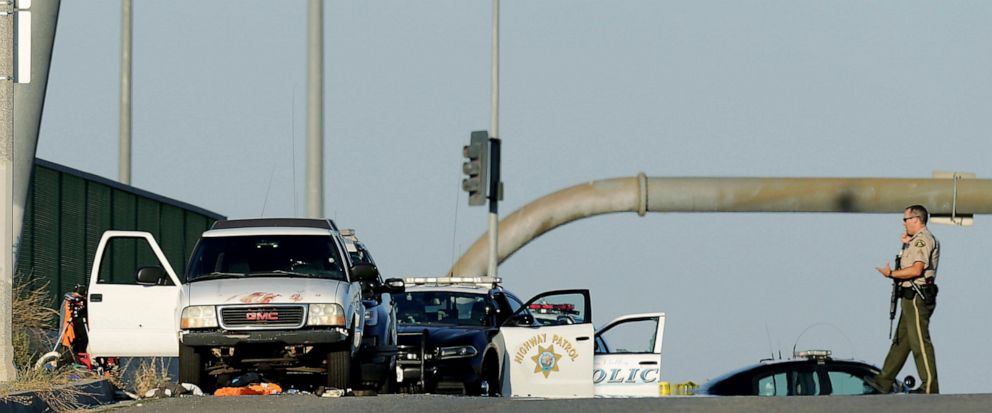 Authorities investigate the scene on the Eastridge Avenue overpass over Interstate 215, where a fatal shootout occurred, Monday, Aug. 12, 2019, in Riverside, Calif. (Terry Pierson/The Orange County Register via AP)