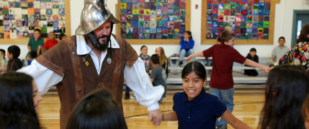 FILE - In this Wednesday, Aug. 30, 2017 file photo, Edwin Quintana, left, dressed as a 17th Century Spanish conquistador, dances with fifth grader Kaylee Pacheco and other students at Tesuque Elementary school in Tesuque, N.M. In recent years, the co