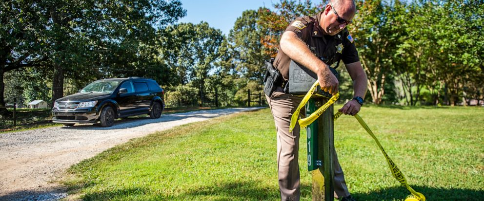 Limestone County Sheriff Sgt. Jonathan Hardiman adds caution tape at the scene of a shooting, Tuesday, Sept. 3, 2019, in Elkmont, Ala. la. A 14-year-old boy admitted to killing five members of his family in Elkmont, including his three younger siblin