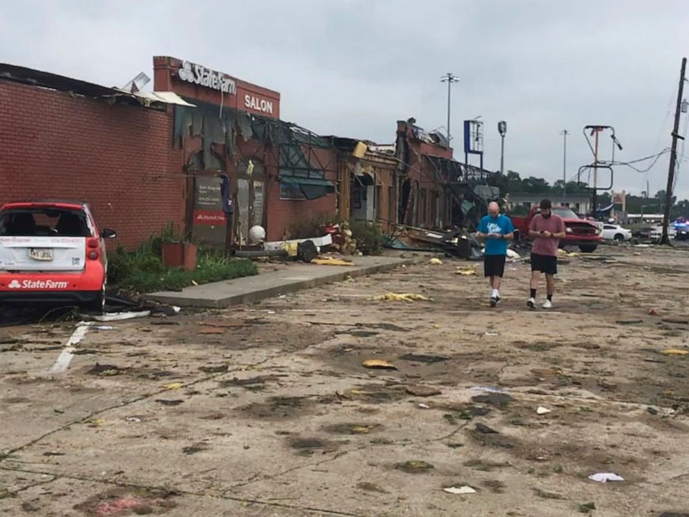 A pair of men walk though the parking lot of a strip mall that was destroyed by a deadly tornado that tore through the northern Louisiana city of Ruston early Thursday, April 25, 2019. (Jonathan Elmer/The Tech Talk via AP)