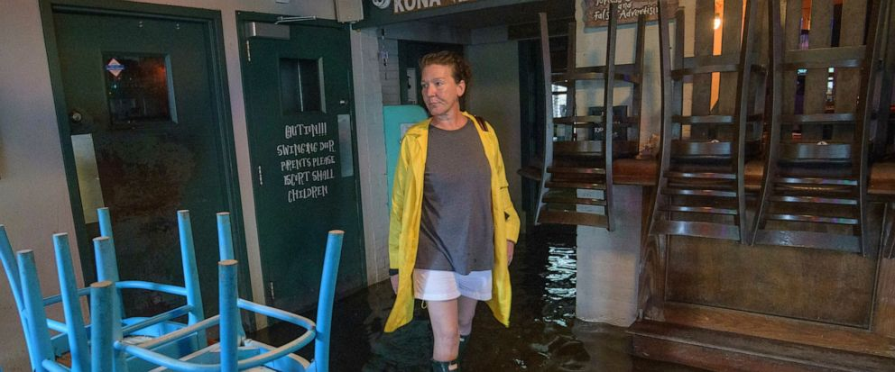 Aimee Cutter the owner of Beach House restaurant walks through water surge from Lake Pontchartrain on Lakeshore Drive in Mandeville, La., ahead of Tropical Storm Barry, Saturday, July 13, 2019. Barry is expected to reach hurricane strength by the tim