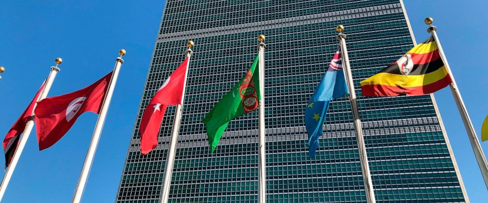 """FILE - In this Sept. 28, 2019 file photo, flags fly outside the United Nations headquarters during the 74th session of the United Nations General Assembly. Secretary-General Antonio Guterres says the United Nations is facing its """"worst cash crisis"""" i"""