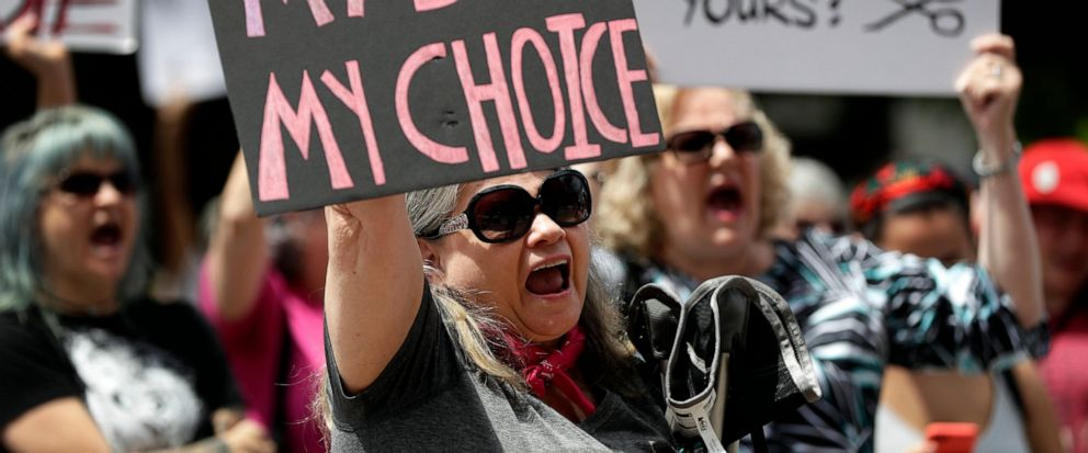 FILE - In this May 21, 2019 file photo, a group gathers to protest abortion restrictions at the State Capitol in Austin, Texas. Arguments over a Texas law requiring that health care clinics bury or cremate fetal remains from abortions and miscarriage