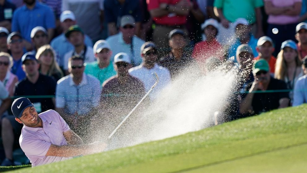 Francesco Molinari, of Italy, hits from a bunker on the 18th hole during the third round for the Masters golf tournament Saturday, April 13, 2019, in Augusta, Ga. (AP Photo/David J. Phillip)