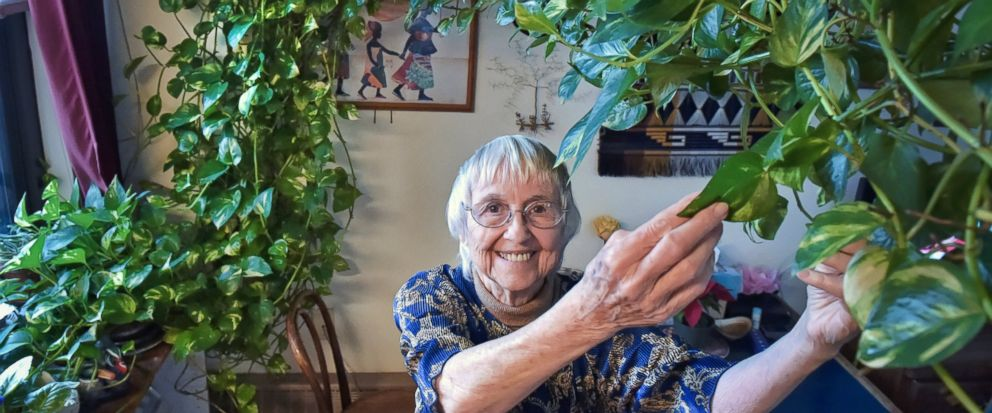 """In this Tuesday, Jan. 8, 2018 photo, Gabrellen """"Gabby"""" Pfarr, poses in her Lancaster, Pa. home, along with her beloved houseplant. Pfarr, whos dying of cancer, is trying to find a home for her 15-foot-long plant. (Dan Marschka/LNP/LancasterOnline via AP)"""
