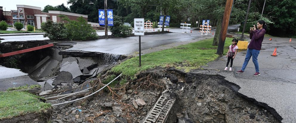 Heavy rains passing through the Pittsburgh area opens up a massive sinkhole Thursday, July 11, 2019, at the intersection of McKnight Circle and McKnight Road in the North Hills neighborhood of Pittsburgh. (Peter Diana/Pittsburgh Post-Gazette via AP)