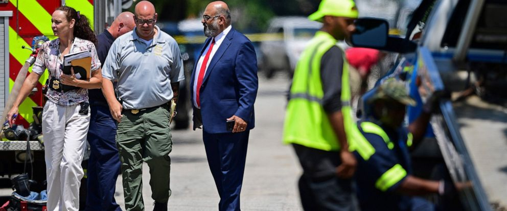 Investigators walk to the crime scene, Tuesday, July 9, 2019, in Cleveland. Police investigating the shooting death of a man in a vacant lot say they also found the bodies of a woman and two children in a nearby house. Authorities arent saying how t