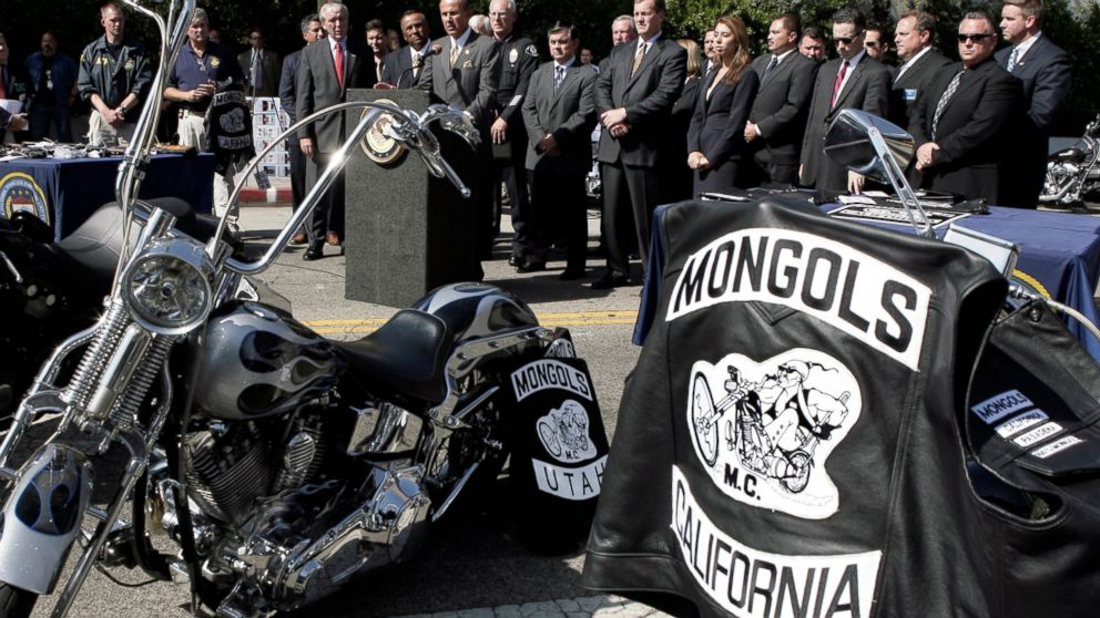 FILE - In this Oct. 21, 2008 file photo, Los Angeles County Sheriff Lee Baca, at podium, speaks during a news conference in Los Angeles with the trademarked Mongols logo seen on a motorcycle at right. A California federal judge has refused to order the Mongols motorcycle gang to forfeit its trademarked logo, delivering a blow to prosecutors. U.S. District Court Judge David O. Carter said Thursday, Feb. 28, 2019, that such an order would have been unconstitutional. (AP Photo/Ric Francis, File)