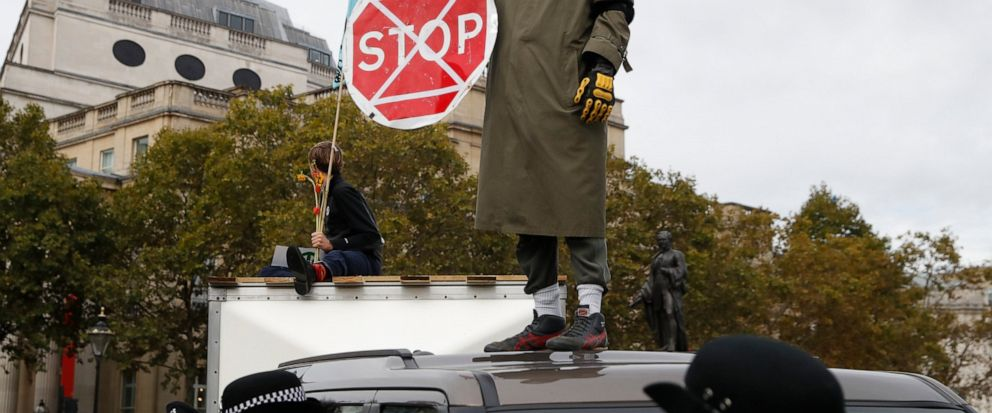 A man wearing a gas mask stand on top of a car as other demonstrators block Trafalgar Square in central London Monday, Oct. 7, 2019. Extinction Rebellion movement blocked major roads in London, Berlin and Amsterdam on Monday at the beginning of what
