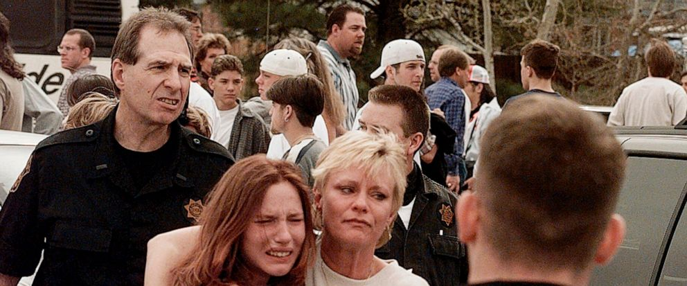 FILE - In this April, 20, 1999, file photo, a woman embraces her daughter after they were reunited following a shooting at Columbine High School in Littleton, Colo. The shooting shocked the country as it played out on TV news shows from coast to coas