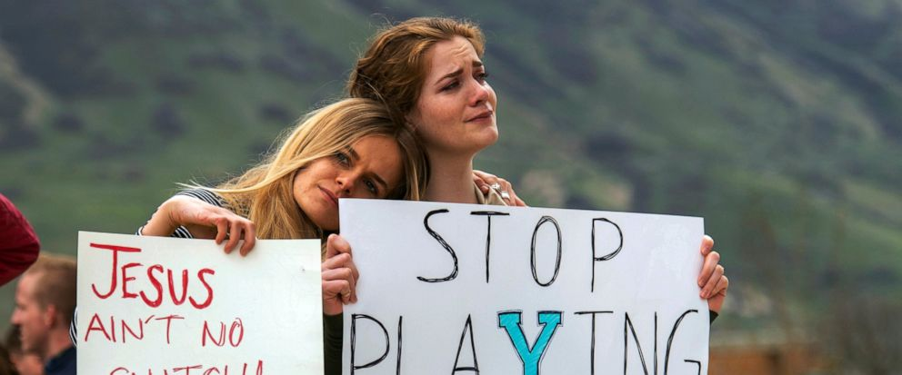 FILE - In this April 12, 2019, file photo, Tyler Slade and Zoe Calcote stand for a moment of silence on the campus of Brigham Young University with hundreds of BYU students at a rally to oppose how the schools Honor Code Office investigates and disc