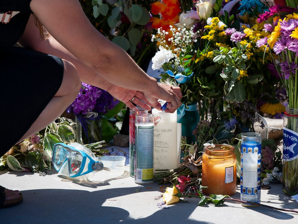 A woman relights a candle placed at a memorial for the victims of the Conception dive boat on the Santa Barbara Harbor on Sunday, Sept. 8, 2019 in Santa Barbara, Calif. Authorities served search warrants Sunday at the Southern California company that